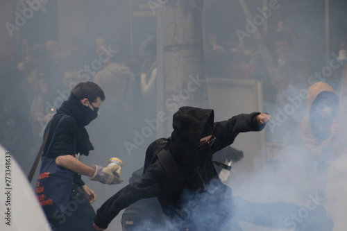 Canvas-taulu Masked protesters throw projectiles at police in response to tear gas