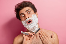 Shocked Young Man Applies Foam, Prepares For Trimming Beard, Holds Razor Blader, Feels Thick And Tired Of Daily Shaving, Poses Over Pink Background. People, Beauty Treatments And Hygiene Concept