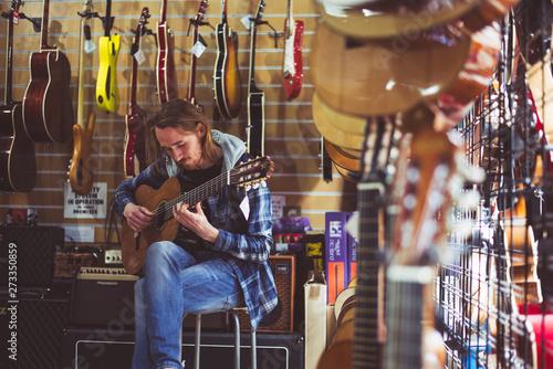 Fotografie, Obraz  Mężczyzna gra na gitarze w sklepie muzycznym
