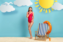 Full Length Shot Of Shocked Lovely Slim Woman Wears Red Bathing Suit, Astonished Hearing Bad News, Recreats At Beach, Deck Chair And Lifebuoy Near, Stands Against Blue Background, Sun Shines Brightly