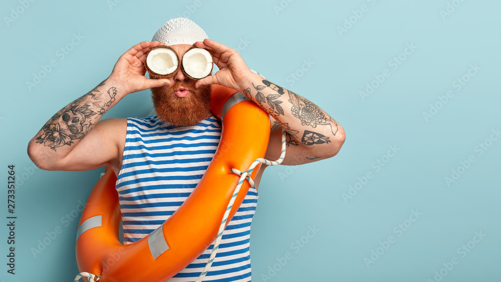 Fototapety, obrazy: Horizontal shot of ginger male sailor looks into distance, uses coconut as binoculars, wears rubber swimhat, blue and white striped vest, has tattoo, models indoor over blue wall with free space