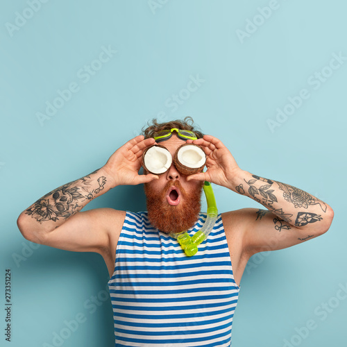 Photo of funny surprised guy covers eyes with coconuts, has thick ginger beard, uses snorkel mask for diving under water, wears striped sailor vest, isolated over blue background. Active rest concept Wall mural