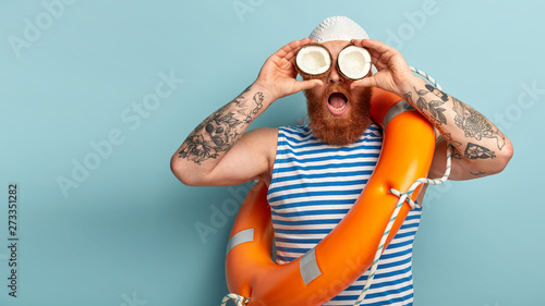 Leinwand Poster Surprised male lifeguard keeps two coconuts, has tattooed arms, wears striped sailor vest, carries orange lifering, cares about safety on water, isolated over blue wall