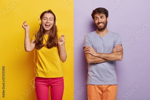 Photo sur Toile Les Textures Optimistic attractive lady listens music in headphones, moves as hears favourite song, closes eyes from pleasure, happy man keeps arms folded, have fun together. People, music, lifestyle concept