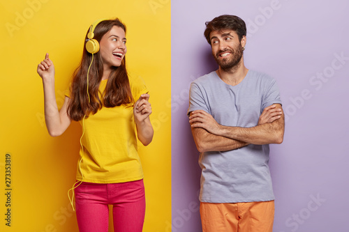 Photo sur Toile Les Textures Positive lovely female dances and listens music in headphones, happy man with arms folded looks at girlfriend, being in good mood, pose over colorful background. People, music, leisure concept