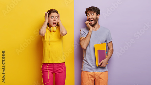 Fotografía  Scared female and cheerful male students prepare for exams, have deadline, puzzl