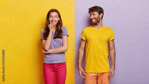 Obraz Optimistic young female and male with broad smiles, feel happy, dressed in casual clothes, have fun together, stand against purple and yellow background. People, relations, togetherness concept - fototapety do salonu