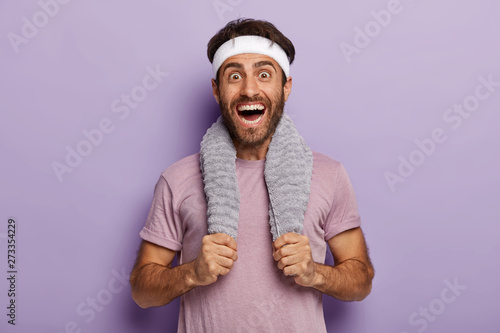 Happy male runner smiles broadly, surprised to cover long distance on marathon, has towel on neck, wears casual t shirt and white headband, isolated over purple background Принти на полотні