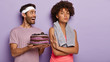 Beautiful confident sport girl with Afro haircut refuses eating sweet cake, shows no gesture, supports healthy nutrition and lifestyle. Happy man wears headband and t shirt suggests dessert to woman