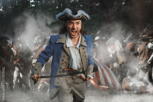 Photo Man dressed as soldier of War of Independence USA attacks with saber in battle