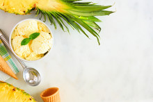Bowl Of Pineapple Coconut Ice Cream. Above View Corner Border Over A White Marble Background. Copy Space.
