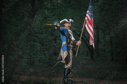 Fotomural Epic Portrait of man dressed as soldier of american revolution war of United States aims from pistol with flag