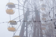 Selective Focus Of Ferris Wheel Attractionron Behind Barbed Wire In Fog In Winter Abandoned Amusement Park In Pripyt, Chernobyl Zone Of Alienation