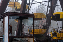 Rust Ferris Wheel Attraction In Fog In Winter Abandoned Amusement Park Overgrown With Trees In Pripyt, Chernobyl Zone Of Alienation