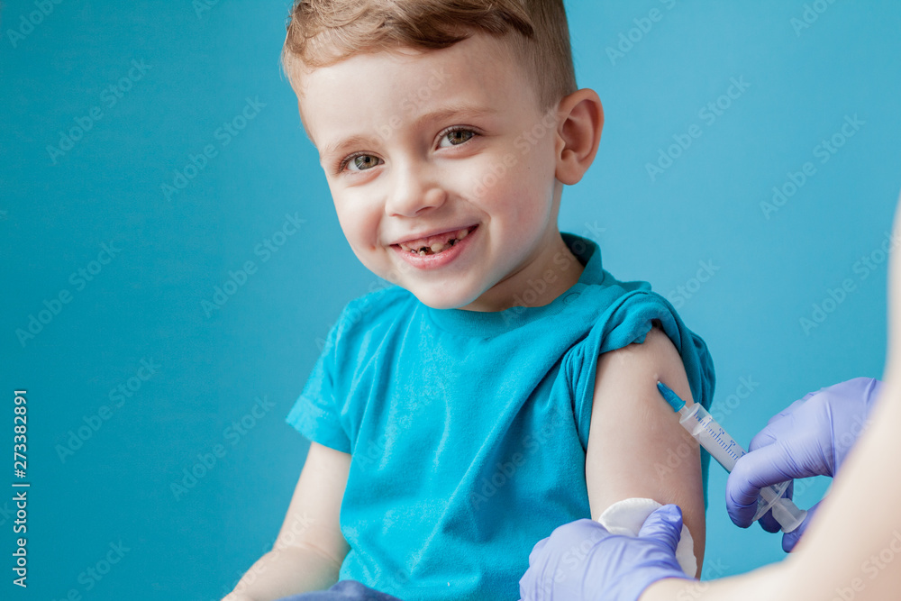 Fototapety, obrazy: Vaccination concept. Female doctor vaccinating cute little boy on blue background, closeup
