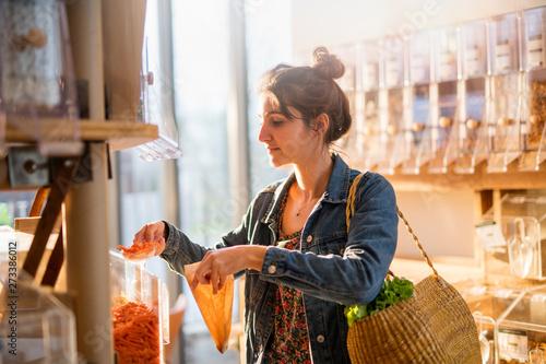 Obraz Beautiful young woman shopping in a bulk food store. - fototapety do salonu