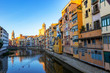 Colorful yellow and orange houses reflected in water, Girona