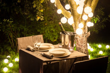Illuminated Table For Two In Evening Garden