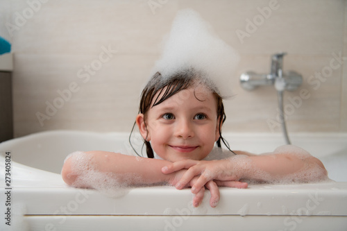 little girl in bath playing with foam Wallpaper Mural
