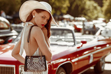 Street Fashion Portrait Of Young Elegant Luxury Woman Wearing Wide Brimmed Hat, Striped Linen Jumpsuit, Pearl Earrings, With Animal Print Zebra Bag, Posing Near Red Retro Car. Copy, Empty Space