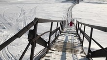 Woman Walks Through A Frozen River Crossing Over The River. Dangerous Descent In Winter Through The Snow, Going Downstairs In A Bright Day