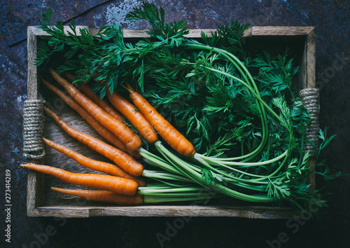 Leinwand Poster Bunch of fresh baby carrots in a wooden box top view space for text