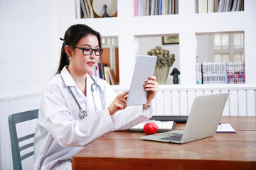 female doctor work with computer and pape note in order to order medical care to nurse for good health of patient at clinic of hospital for health care