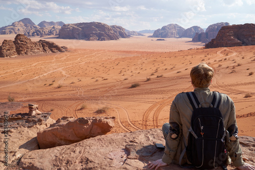 Traveler posing in red Wadi Rum desert in Jordan and admires the view to scenic landscape with dunes Wallpaper Mural