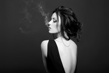 Art Brunette Woman Smoking On Dark Background In Black Dress. Classic Portrait Of A Confident Strong Woman
