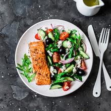 Healthy Mediterranean Lunch - Grilled Fillet Salmon And Vegetables, Olives, Feta Greek Salad On Dark Background, Top View