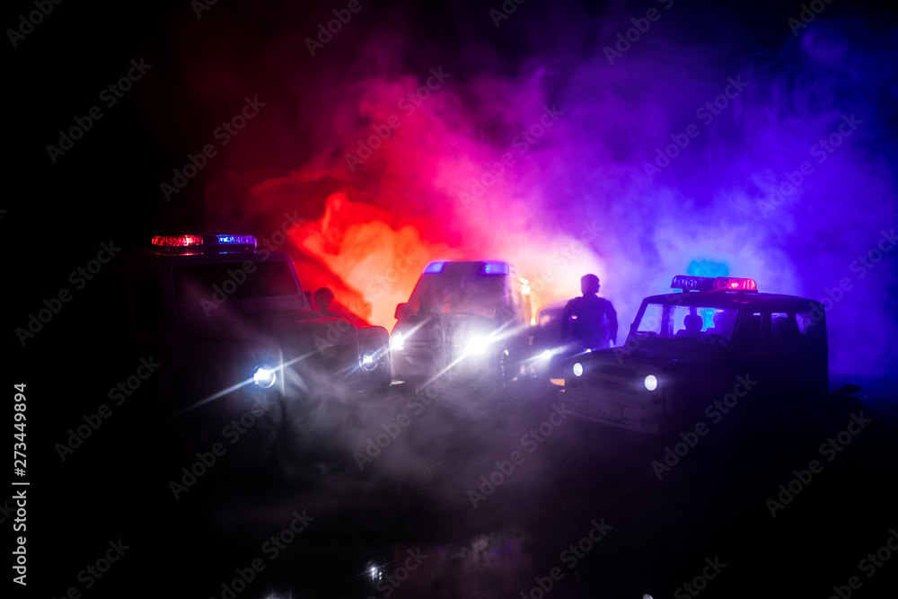 Fototapeta Police cars at night. Police car chasing a car at night with fog background. 911 Emergency response pSelective focus