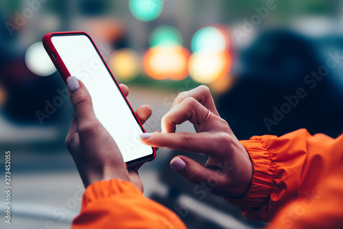 Fotomural  Close up view of female hands holding mobile phone touching mock up blank screen with finger
