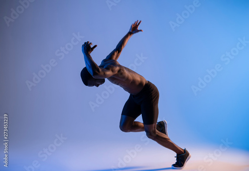 Fotografiet  Unrecognizable African-American sprinter man running extremely fast in blue ligh
