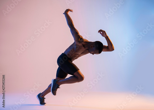Fotografering  Muscular Shirtless African-American man sprinting in red and blue light