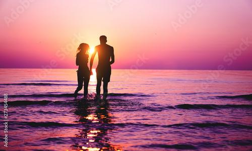 Fotografia Silhouette of couple in love running inside ocean water at sunset - Lovers havin
