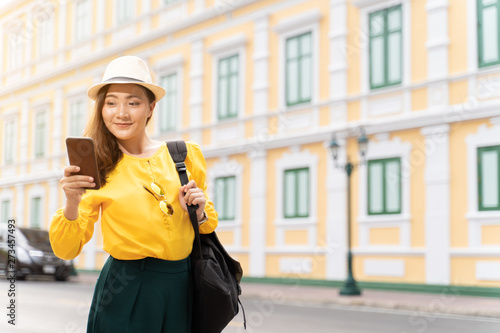 Happy tourist woman used smart phone for searching the street locations Wallpaper Mural