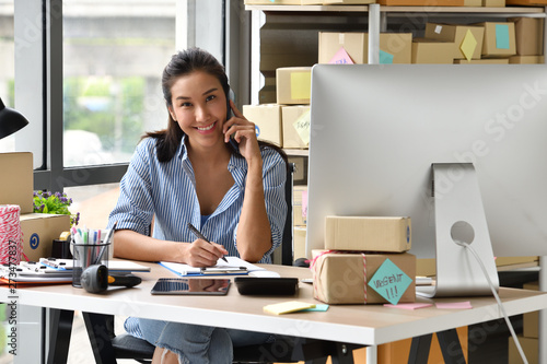 Fotomural  Young Asian woman entrepreneur/ Business owner working with computer at home