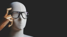 Close Up White Mannequin With Eyeglasses In Thinking And Having Idea Gesture On Black Background