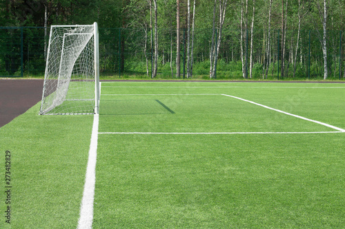 Obraz Football goal in the field. From which the shadow on a green grass falls. A look with a side. - fototapety do salonu