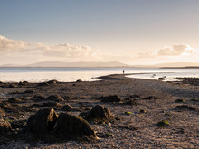 Girl Is Standing On A Small Path To Hare Island, Galway, Burren Mountains In The Background. Concept: Adventure, Explore.