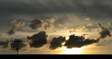Beautiful Golden Yellow Dramatic Sunset Cloudy Windy Sky Setting Sun Clouds Timelapse With Antenna And Roof Foreground