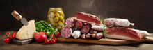 Italian Food. Various Kind Types Of Salami, Speck, Sausages, Parmesan Cheese, Olives, Basil And Fresh Tomatoes