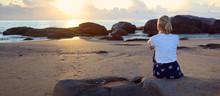 Woman Sitting On Rocks Watching Sunrise On A Deserted Beach