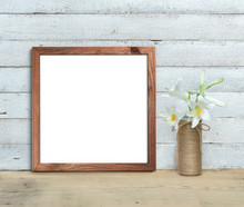 Square Old Wooden Frame Mockup Near A Bouquet Of Lilies Stands On A Wooden Table On A Painted White Wooden Background. Rustic Style, Simple Beauty. 3d Render.