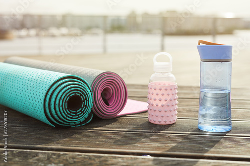 Obraz Background image of yoga mats and water bottles set for workout on wooden pier outdoors, copy space - fototapety do salonu