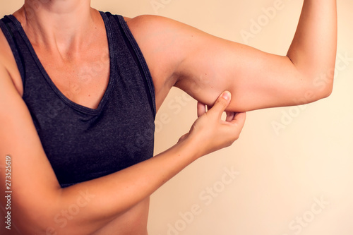 Fotografia, Obraz Woman touches her tricep. People, healthcare and beauty concept