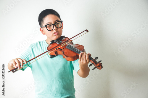 The little Asian boy is playing and practicing the violin in the white room. - 273528460
