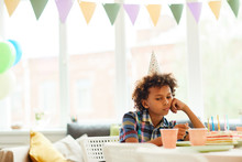 Portrait Of Sad African-American Boy Sitting Alone At Birthday Party, Copy Space