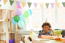 Portrait Of Sad African-American Boy Sitting Alone At Birthday Party In Decorated Room, Copy Space