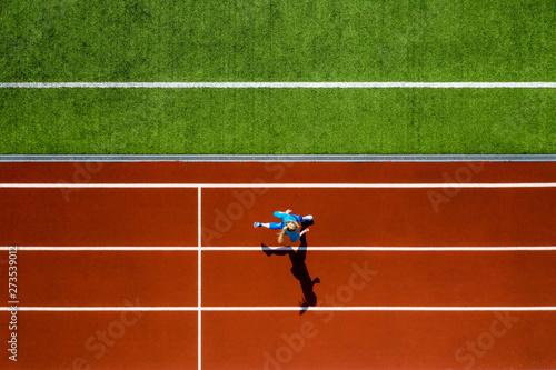 Fototapeta Sportive blonde woman running at open stadium obraz